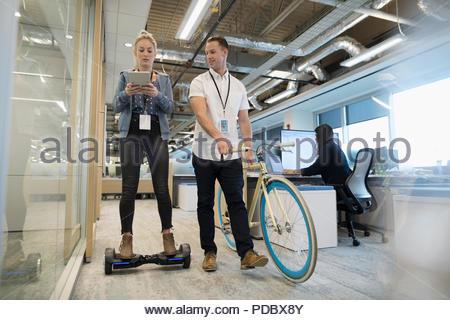 Kreative Geschäftsfrau mit digitalen Tablette auf Hoverboard, im Gespräch mit Geschäftsmann Wandern Fahrrad im Büro - Stockfoto