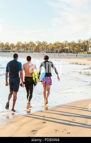 Männliche Surfer gehen mit Surfboards an sonnigen Strand - Stockfoto
