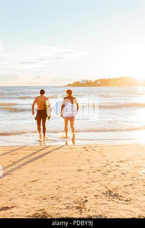 Männliche Surfer, die surfbretter in Ozean auf Sunny Beach - Stockfoto