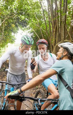 Männliche Freunde Mountainbiken, mittels Smart Phone in Wäldern - Stockfoto