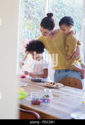 Mutter zur Tochter Frühstück am Tisch serviert - Stockfoto
