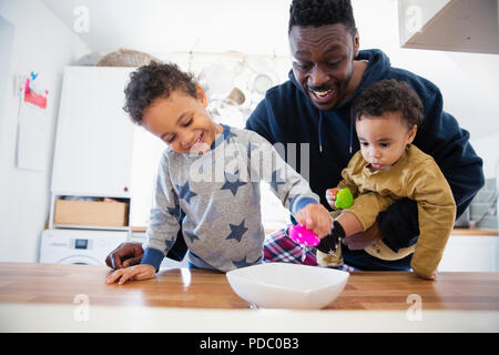 Vater und Söhne mit Spielzeug spielen in der Küche - Stockfoto