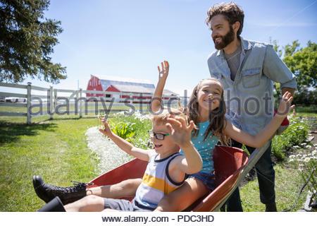 Verspielt Vater, Tochter und Sohn in der Schubkarre im sonnigen ländlichen Garten - Stockfoto