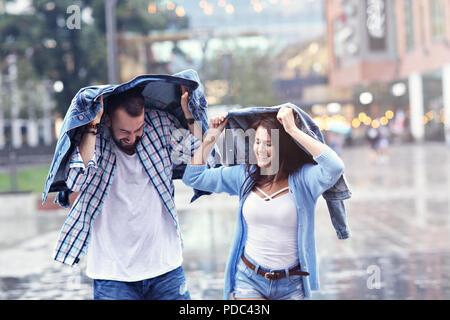 Glückliches Paar Laufen im Regen in der Stadt - Stockfoto