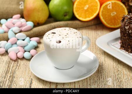 Tasse Cappuccino mit Cookies und Löffel serviert. - Stockfoto