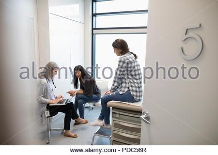 Ärztin mit Laptop im Gespräch mit Mutter und Tochter Patienten in Klinik Untersuchungsraum - Stockfoto