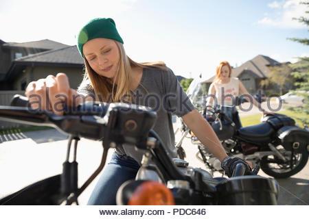 Junge Frauen, die Freunde mit Motorrädern im sonnigen Auffahrt - Stockfoto