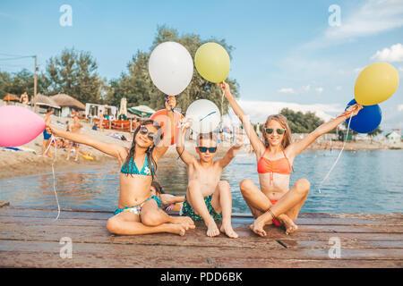 Glückliche Kinder spielen mit Ballons im Meer. Kinder Spaß im Freien. Sommer Urlaub und gesunden Lebensstil Konzept - Stockfoto