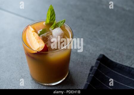 Pfirsich Bourbon Cocktail mit Pfirsich Slice, Minze und Eis. Im Sommer trinken. - Stockfoto