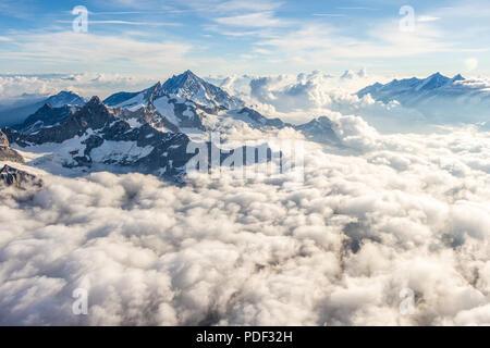Ein Blick auf die beeindruckenden Spitzen über ein Meer von Wolken an einem klaren Tag - Stockfoto