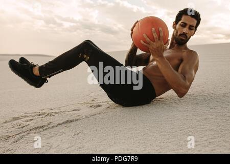 Starker junger Mann, einen medizinball Workout auf Sanddünen. Sportler mit einem medizinball für Fitness Training an der Wüste. - Stockfoto