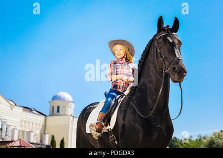 Blonde Schülerin tragen Cowboyhut sitzen auf schwarzen Pferd - Stockfoto