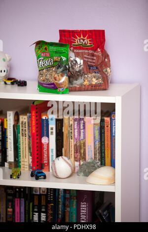Plastiktüten von hamster Essen sitzen auf einem Bücherregal - Stockfoto