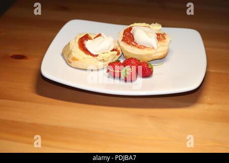 Gebäck und Marmelade auf einem weißen Teller mit frischen Erdbeeren - Stockfoto