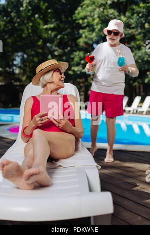 Pensionierte liegende Frau auf der Liege warten auf Cocktails - Stockfoto