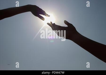 Zwei Hände, die versuchen, sich vor der Sonne zu verbinden - Stockfoto