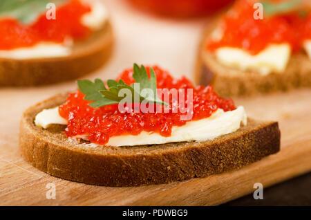 Sandwiches mit imitierter roter Kaviar und Butter auf Holz Schneidebrett auf hölzernen Tisch - Stockfoto