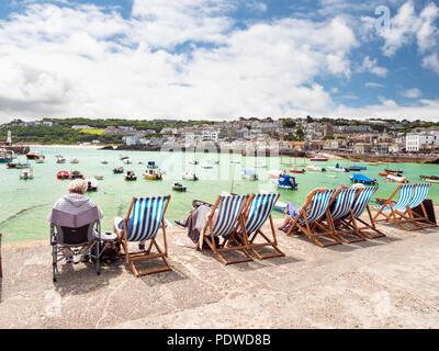 St. Ives, ENGLAND - Juni 19: ältere Urlauber, sitzen in einer Reihe von Liegestühlen und genießen die Sonne Sommer in St. Ives, Cornwall. In St. Ives, England. - Stockfoto