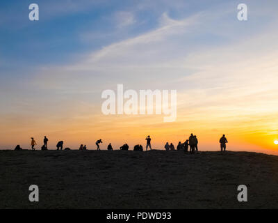 Gruppe von Menschen in Silhouette genießen Sie einen bunten Sonnenuntergang auf den Felsen. Männer und Frau in Outdoor Freizeitaktivitäten Aktivität. Urlaub und sehen die Welt conc - Stockfoto