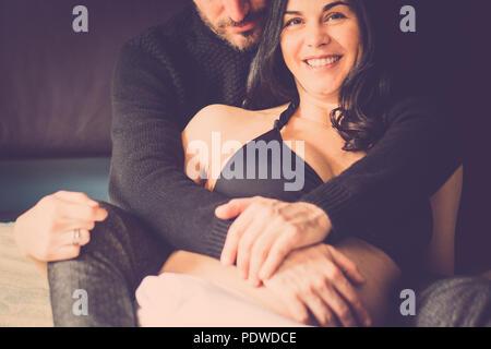 Paare, die in Liebe zu Hause legte sich auf das Bett lächeln und schauen sich gegenseitig mit Zärtlichkeit. Kaukasier, Innen- Aktivität. Sie schwanger für neue Familie und - Stockfoto