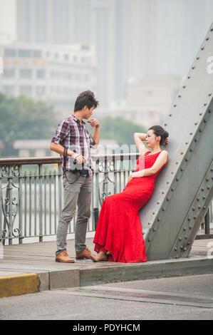 Shanghai, China - 20. Oktober 2014. Fotograf und ein weibliches Model beim Fototermin auf einer Brücke über den Fluss Huangpu in Shanghai. - Stockfoto
