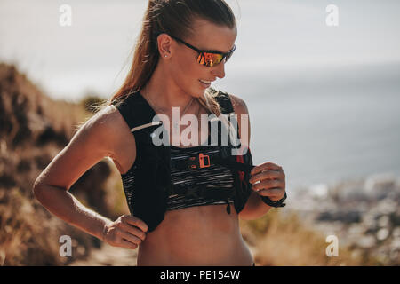 Close up Portrait von gesunden jungen Frau, die im Freien auf einem Berg Trail. Zuversichtlich Läuferin mit Sonnenbrille, die Pause während der Ausbildung - Stockfoto