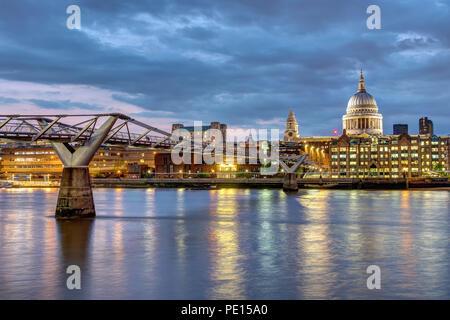St. Paul's Cathedral und die Millennium Bridge in London, Großbritannien, nach Sonnenuntergang - Stockfoto