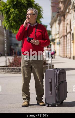 Älterer mann Tourist hat die Stadt in den Urlaub kommen, aber er nicht weiß, welcher Weg zu gehen. Bild ist absichtlich abgeschwächt. - Stockfoto