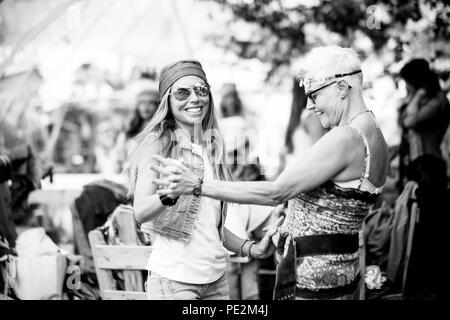 Junge Frauen und Mädchen in Freundschaft alle zusammen feiern und Spaß haben in einem Bio natürliche Ort. Lächeln und Lachen für die Gruppe von Hippies Menschen al