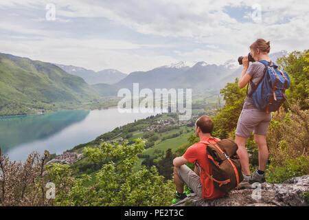 Reise und Tourismus, ein paar Reisende mit Rucksäcken mit Panoramablick auf See, Wanderer entspannen auf oben auf den Berg - Stockfoto