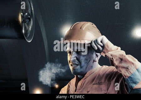 Portrait von müde Schiene Arbeiter mit orange unifom und Helm Licht vor dem Tunnel in der Nacht - Stockfoto