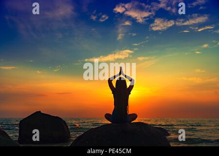 Menschen Yoga und Meditation am tropischen Strand bei Sonnenuntergang - Stockfoto