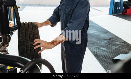 7/8 Schuß von einem Mechaniker, Autoreifen checkup im Service Station. Mann Inspektion der Grip in der Werkstatt. - Stockfoto