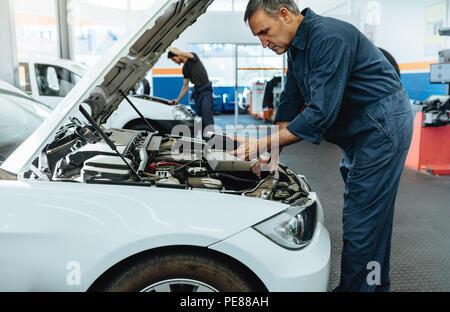 Automechaniker mit Diagnose Gerät für das Lesen der Fehlercodes. Mechanische Prüfung des Auto Service Station. - Stockfoto