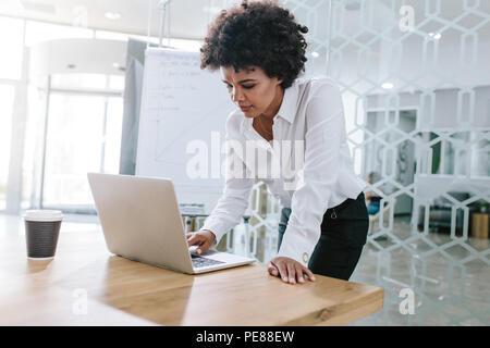 Afrikanischer junge Frau, die durch die Tabelle und auf Ihrem Laptop. Business woman Arbeiten am Laptop im Konferenzraum. - Stockfoto