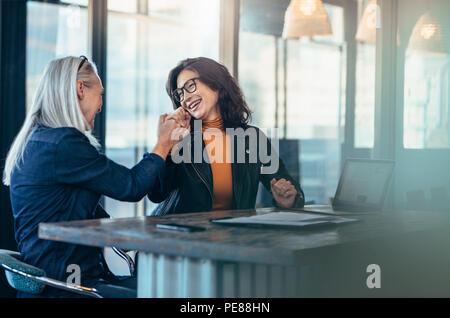 Zwei Business woman geben einen hohen fünf und lächelnd. Office Mitarbeiter Erfolg freuen. - Stockfoto