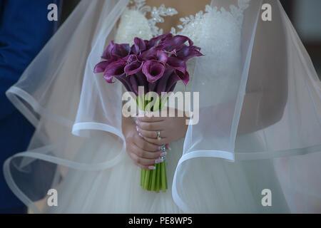 Kaukasische Braut tragen zu einem opulenten Hochzeit Kleid mit großen Tüll Schleier und halten eine anspruchsvolle Pflaume calla Lilien Brautstrauß - Stockfoto