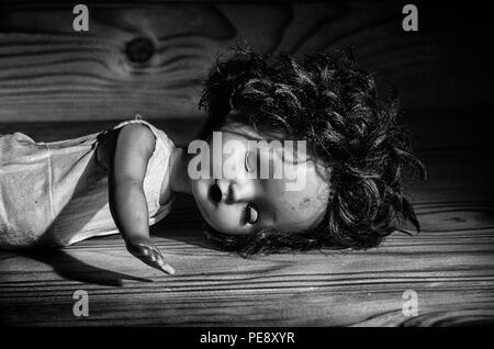 Eine alte kaputte Puppe auf einem Holztisch in Schwarz und Weiß. - Stockfoto