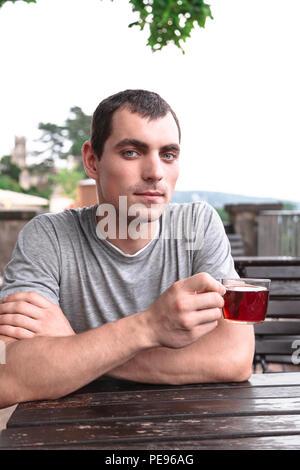 Junge Mann hält Tasse Kaffee in einem Cafe - Stockfoto