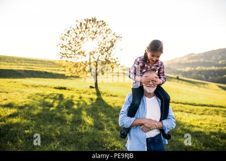 Ein älterer Großvater eine kleine Enkelin eine piggyback Ride in der Natur. - Stockfoto