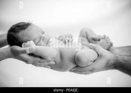 Cute Baby schläft in den Händen der Eltern geschützt und sicher - happy family Momente für Mama und Papa - Stockfoto