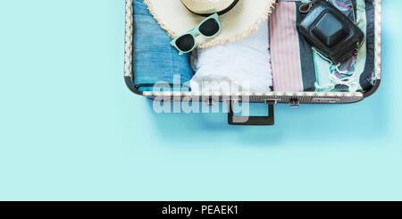 Koffer mit weiblicher Kleidung Offen für Reise auf Pastell blau. Ansicht von oben mit der Kopie. Sommer Konzept reisen. - Stockfoto