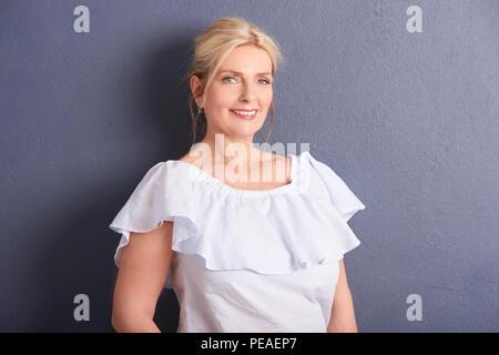 Porträt einer wunderschönen alten Frau an der Kamera schauen und lächeln, während gegen an der grauen Wand posieren. - Stockfoto