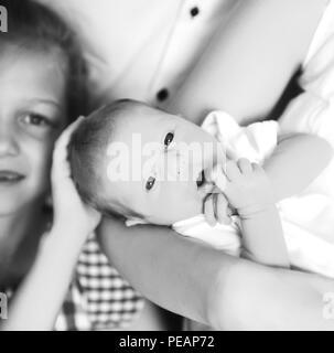Ältere Schwester neben einem neugeborenen Baby - Stockfoto