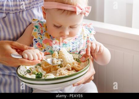 Closeup Porträt der jungen Frau, die Mutter ihre Tochter Tochter füttern mit Gemüse Brokkoli Blumenkohl. Gesunde organische Lebensmittel für Kinder. Candid lifes