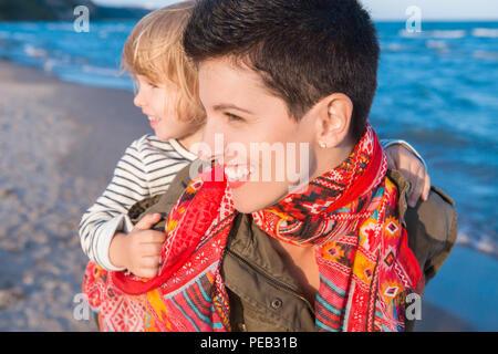 Group Portrait von lächelnden weißen weißen Mutter und Tochter baby girl, Huckepack, Reiten, Spielen, die auf Ozean Meer Strand bei Sonnenuntergang im Freien, Hap - Stockfoto