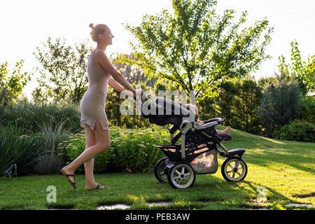 Junge hübsche Mutter mit Baby im Kinderwagen geniessen Wandern in Grün frisch Garten bei Sonnenuntergang. Mom-Spaß mit Baby im Kinderwagen in den wunderschönen Park. Glückliche Mutterschaft Konzept - Stockfoto
