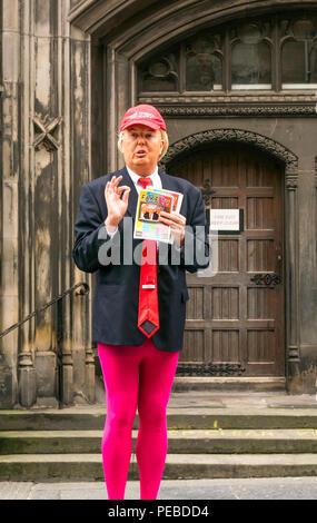 Edinburgh, Schottland, Großbritannien. 14. August 2018. Edinburgh Fringe Festival Performer, Royal Mile, Edinburgh, Schottland, Vereinigtes Königreich. Eine dumme Donald Trump Imitator tragen Tragen eines Baseball Cap mit Amerika Gay wieder und rosa Strumpfhose verteilen Flyer für eine Franse zeigen - Stockfoto
