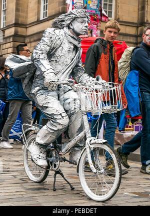 Edinburgh, Schottland, Großbritannien. 14. August 2018. Edinburgh Fringe Festival Street Performer, Royal Mile, Edinburgh, Schottland, Vereinigtes Königreich. Eine lebende Statue Street Performer auf einem stationären Fahrrad weiß lackiert mit vortäuschen, fliegende Haare und Schal - Stockfoto