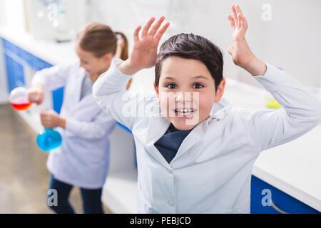 Interessant Chemie. Gerne schön smart Boy seine Hände und suchen Sie während der Durchführung ein chemisches Experiment - Stockfoto